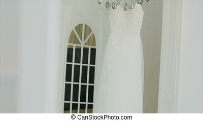 Wedding dress hanging in a white beautiful room