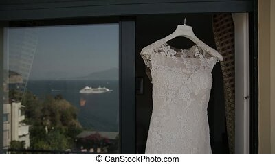 Wedding dress hanging in doorway, background blue sea