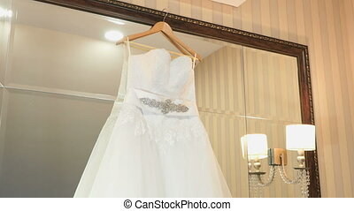 Wedding dress hanging on a shoulders indoors. Wedding...