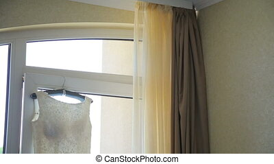 Wedding dress hanging on a window