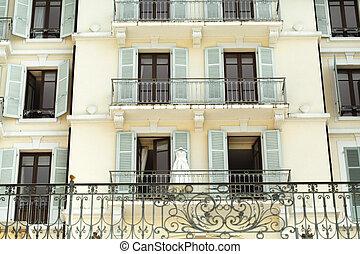 Wedding dress hanging on old luxury hotel window architecture landscape