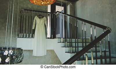 Wedding dress hanging on the stairs.