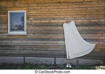 Wedding dress on a hanger against a Bar wall 1590.