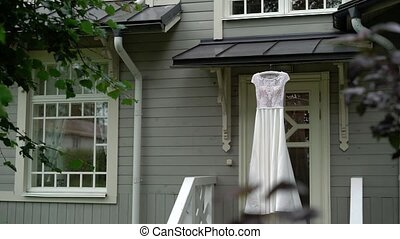 Wedding dress outdoors on old wooden building