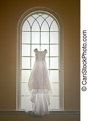 Wedding Dress hung in a beautiful window.