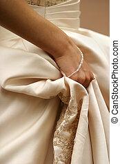 Wedding dress - The bride holds a hem of a wedding dress