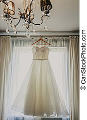 Wedding dress. White wedding dress with a full skirt on a hanger in the room of the bride with white curtains. Wedding attributes. No people.