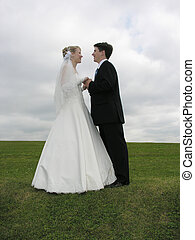 wedding face to face on grass and clouds