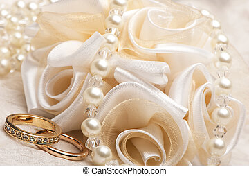 wedding favors and wedding ring on on colored background