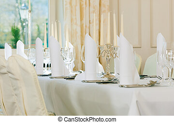 Wedding - feastfully decorated table with silverware and...