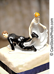wedding figurine on cake with bride dragging the groom doll by the feet to the church symbolically