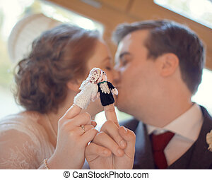 Wedding Finger Puppet Kiss - Married couple kissing with his...