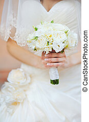 Wedding Flowers Bouquet in Bride Hands with White Dress on Background