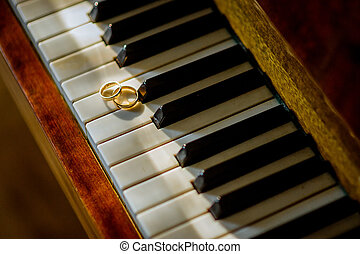 Wedding gold rings on the piano. Closeup. Love concept. Bride and groom accessories.