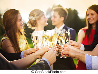Wedding guests clinking glasses while the newlyweds hugging...