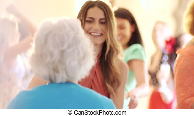 Guests are dancing together at a wedding. A senior woman is dancing with a young woman.