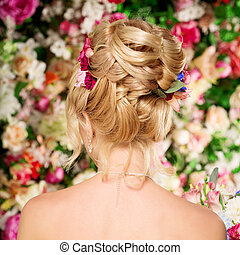 Wedding hairstyle a young girl. Bride. Woman with Flowers in her hair. High stacking, a bundle of curls. Beautiful blonde model. Earrings and bouquet
