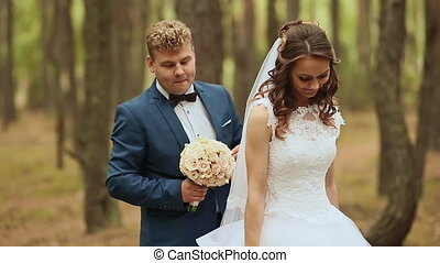 Wedding. Happy couple in a forest in the fresh air. Elegant groom behind bride. In the hands of a beautiful bouquet of roses. Bride turns, receives a bouquet. Couple embrace each other.