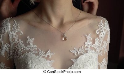 Wedding. Jewelry. The bride in a white dress putting on a necklace around her neck