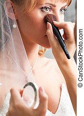bride is doing make up for wedding celebration