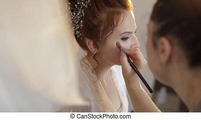 Wedding makeup artist making a make up for bride in veil....