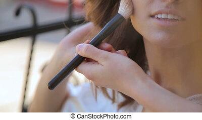 Wedding makeup for a young bride - face closeup applying tone powder