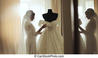 Wedding morning. Bride's preparations holding and admiring...