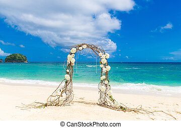 Wedding on the beach . Wedding arch decorated of vines and...