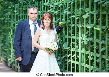 Wedding people with green fence, copyspace
