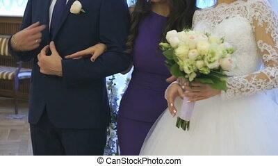 Wedding photo shoot indoors. The newlyweds and girlfriend of...