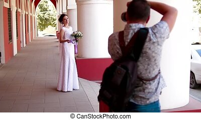 Wedding photographer taking portraits of young beautiful bride near the columns