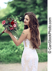 Wedding Portrait Of Beautiful Bride with long wavy hair wearing in white lace wedding dress