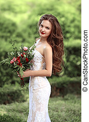 Wedding Portrait Of Beautiful Bride with long wavy hair wearing in white lace wedding dress holding with bouquet of rose flowers posing in green park.