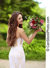 Wedding Portrait Of Beautiful Happy Bride with long wavy hair wearing in white lace wedding dress holding with bouquet of rose flowers posing in green park.