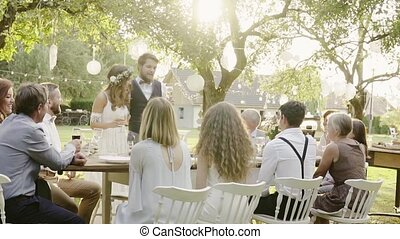 Wedding reception outside in the backyard. Bride and groom...