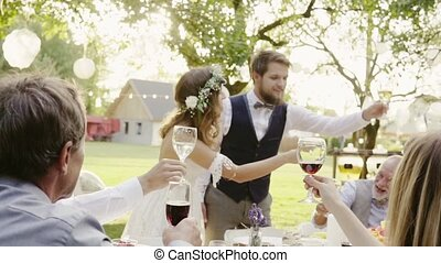 Wedding reception outside in the backyard. Bride, groom and...