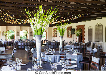Wedding reception venue with decorated tables and fairy...