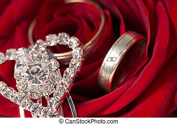 red rose and small diamond encrusted hearts with wedding rings