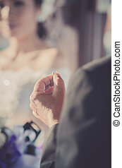 Wedding ring in groom hand.