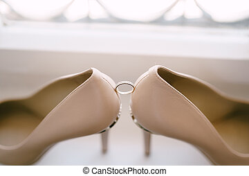 Wedding ring of the bride on a white background with the bride's shoes in beige.