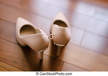 Wedding ring on the bride's cream shoes on a blurred background.