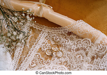 Wedding rings and an engagement ring white wedding dress of the bride with lace and wildflowers on a wooden table.
