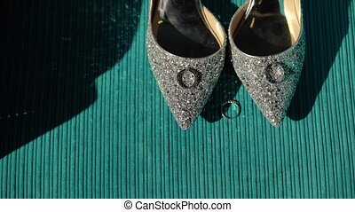 Wedding rings and bridal shoes indoors