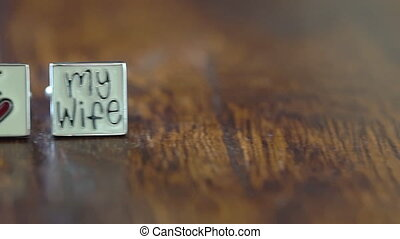 Wedding Rings and Cufflinks on the Wooden Table - Golden...