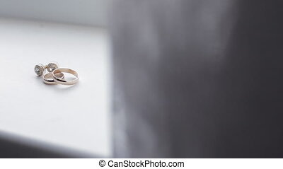 Wedding rings and earrings on window-sill