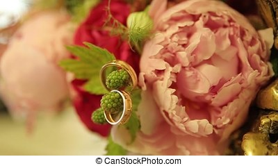 Wedding rings and pink rose bouquet. Wedding rings on a wedding bouquet. Wedding rings on a bouquet of roses.