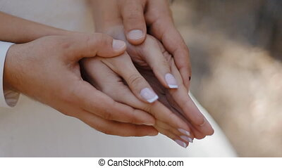 Wedding rings appear in the opening hands. Wedding photo session.
