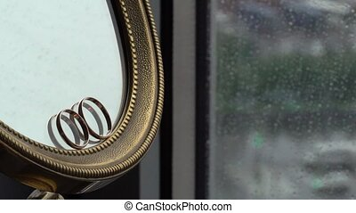 Wedding rings at the mirror indoors