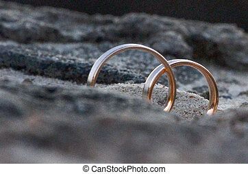 Wedding rings embedded in the sand of the beach
