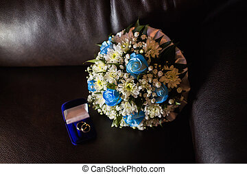 Wedding rings in a blue box, a bridal bouquet of white flowers and blue roses on a blue background temnof, preparing for the wedding